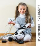 Small photo of Cute little girl dangerously playing with sockets and electricity while her parents absent