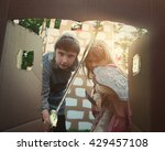 Small photo of Children are dressed in a knight and princess costumes looking in a door of a cardboard castle for a creative imagination concept.