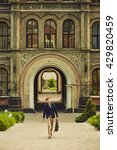 Stock photo handsome male student walking in front of university building in school uniform carrying bag 429820459