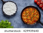 Small photo of Chicken tikka masala traditional Asian spicy butter meat food with tomatoes, parsley and rice in cast iron skillet