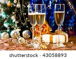 Glasses of champagne with gold ribbon gifts - stock photo