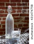 Bottle of cold water in hot summer day on brick wall background - stock photo