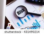 "magnifying glass on ""risk"" text ... 