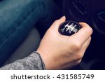 Female driver hand shifting gear manually, selective focus - stock photo