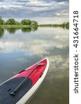 Small photo of red stand up paddleboard with a paddle on calm lake - Arapaho Bend Natural Area, Fort Collins, Colorado