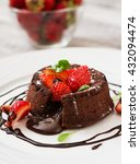 Small photo of Chocolate fondant (cupcake) with strawberries and powdered sugar