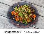 Small photo of Top view of salad plate. Salad plate on wooden background. Healthy dish from european cuisine. Salad with salmon and herbs.