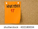 Small photo of 17 NOVEMBER written on orange paper note pinned on cork board with white thumbtacks, copy space available
