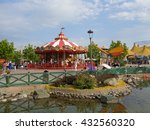 People relax in the amusement park, children ride on the carousel, a pond and green trees, Russia, Sochi Park, June 1, 2016 - stock photo
