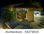 Luxurious mansion exterior at dusk with Bali hut and bar - stock photo