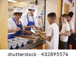 Stock photo two women serving food to a boy in a school cafeteria queue 432895576