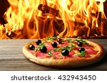 Small photo of Tasty pizza with salami and olives on wooden table against fire flame background