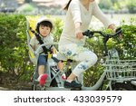 Small photo of parent and kid enjoin cycling