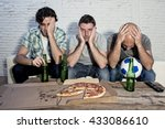 Small photo of group of friends fanatic football fans watching soccer game on television with beer bottles and pizza suffering stress and crazy nervous on couch sad and dejected as if their team is loosing