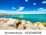 Small photo of breakwater in the Adriatic Sea off the coast with ancient and modern buildings