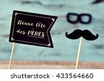 Small photo of a black flag-shaped signboard with the text text bonne fete des peres, happy fathers day in french, and a mustache and a pair of eyeglasses forming the face of a man, against a blue rustic background