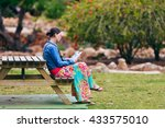 Woman Sitting At Table In...