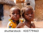 Small photo of ACCRA, GHANA - MARCH 6, 2012: Unidentified Ghanaian girl carries her little brother on his back in the street in Ghana. Children of Ghana suffer of poverty due to the unstable economic situation
