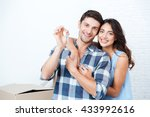 Young Smiling Couple Showing...