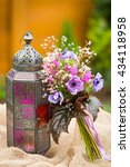 Small photo of Garden stile summer bouquet. Mix of lilac and purple anemone flowers, geranium flowers and heuchera or alumroot leaves. Bouquet with indian stile lantern. Garden stile wedding bouquet. Flower design.