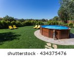 Small photo of An above ground pool sets on a concrete pad in the backyard on a sunny summer day.