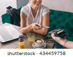 Small photo of Woman pay with credit card in cafe bar