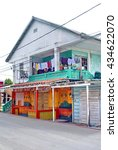 Small photo of AMBERGRIS KEY, BELIZE - CIRCA MAY 2014: Restaurant with a house on the upper story in a wooden building, laundry on the balcony