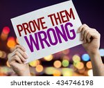 Small photo of Prove Them Wrong placard with night lights on background