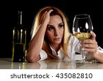 Small photo of drunk blond woman alone in wasted depressed expression looking thoughtful with white wine bottle holding glass isolated on black background in alcohol abuse and alcoholic housewife concept