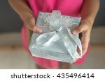 a girl child holding a gift box. | Shutterstock . vector #435496414