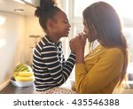 mother kissing her daughter at... | Shutterstock . vector #435546388