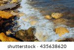Small photo of Tide and sea, beach under cloudy skies. Slider shot featuring sand beach and surf hitting the rocks. Sparkling ocean sea water waves surface & coastal rock reef coast surge shore.
