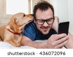 Stock photo man with glasses in blue shirt laying on the bed with the dog and using smart phone 436072096