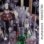 Small photo of Close up of vintage bottles in old laboratory. Halloween, ancient pharmacy or historical science concept. Black magic and occult objects, alchemy equipment on witch table