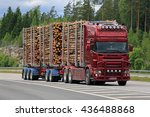 Small photo of PAIMIO, FINLAND - JUNE 10, 2016: Red Scania logging truck hauls pulp wood along freeway. The bioproduct mill of Metsa Group, currently under construction, will increase the demand of pulp wood.