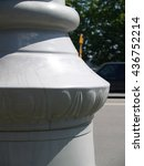Small photo of Closeup of marble column base against city street abd trees