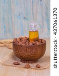 Small photo of almond oil and almonds seed on wooden background