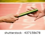 Small photo of Man passing the baton to partner on track against close up of the track starting point