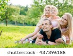 young family lying on grass in... | Shutterstock . vector #437396188