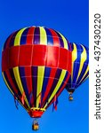 Small photo of Many brightly colored hot air balloons aloft in early morning blue sky