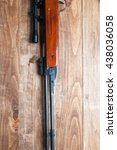 Small photo of Air rifle isolated on wooden backgound