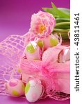 pink tulips  and colored eggs in pink basket as easter decoration - stock photo