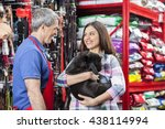 Stock photo salesman looking at customer with bulldog in pet store 438114994