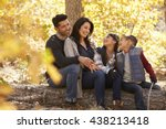 Family Sitting On Fallen Tree...