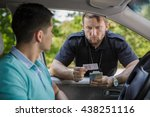 Small photo of Shot of a traffic policeman checking a driving licence