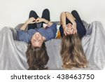 two girls laying upside down on ...   Shutterstock . vector #438463750