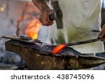 Black smith,Ironsmith hitting hotsteel on an Anvil in a Retro smithy in Chiang Mai Thailand