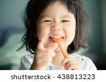happy little asian girl eating... | Shutterstock . vector #438813223