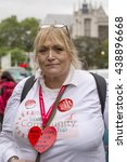 Small photo of London, United Kingdom - June 18, 2016: Jo Cox. A woman in Parliament Square visiting the impromptu memorial site to Jo Cox, the murdered Member of Parliament, wears her heart outside.