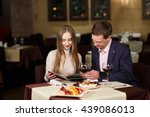 cheerful couple with menu in a... | Shutterstock . vector #439086013